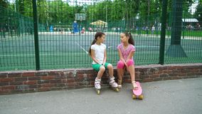 Two children telling secrets and laughing in park, outdoors. Leisure time park stock footage