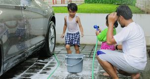 Two children and their father playing water. Two happy children and their father playing water with a water hose while washing their car at home. Shot in 4k stock video
