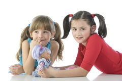 Two children with their favorite dolls Stock Image