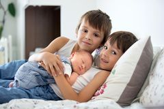 Two children, toddler and his big brother, hugging and kissing t. Heir newborn baby brother at home, few days after delivery Stock Images