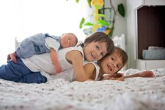 Two children, toddler and his big brother, hugging and kissing t. Heir newborn baby brother at home, few days after delivery Stock Photo