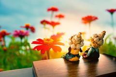 Two children toy sitting and watching flowers. In the garden Royalty Free Stock Images