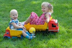 Two children on trucks Royalty Free Stock Photo