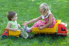 Two children on trucks Stock Photography