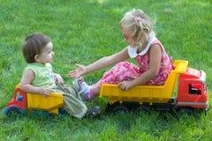 Two children on trucks Stock Photography