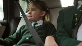 Two Children In Uniform Being Driven To School. Boy and girl sit in back seat of car talking on  car journey to school.Shot on Canon 5d Mk2 with a frame rate of stock video