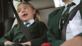 Two Children In Uniform Being Driven To School. Boy and girl sit in back seat of car talking on  car journey to school.Shot on Canon 5d Mk2 with a frame rate of stock footage