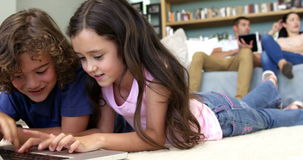Two children are using computer while parents are using pad. Two children are using computer  in the lounge stock video