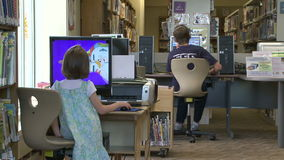 Two children using the computers at the library. A view or scene from a Library stock video