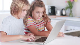 Two children using laptop. In kitchen stock footage
