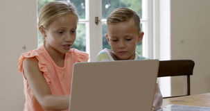 Two children using laptop with mother stock video