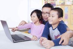 Two children using laptop with teacher in class Stock Image
