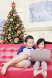 Two children using laptop together on sofa Stock Photography
