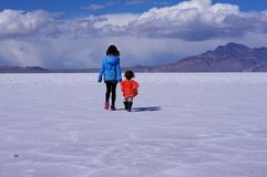 Two children walking across dry lake bed Stock Photos
