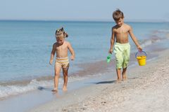 Two children walking by sand beach Stock Images