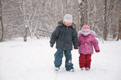 Two children walking in snow Royalty Free Stock Photos