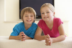 Two Children Watching Widescreen TV At Home Royalty Free Stock Images