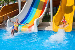 Two children on water slide at aquapark. Stock Photo