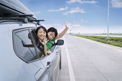 Two children waving hands in the car Royalty Free Stock Photo