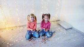 Two kids waving hands at home christmas party. Two children waving hands  at home christmas party on lights background on New Year eve. Girld having fun and stock video footage
