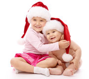 Two children wearing red Christmas caps and smile Stock Photo