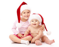 Two children wearing red Christmas caps and smile Stock Images