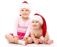 Two children wearing red Christmas caps and smile Royalty Free Stock Photo