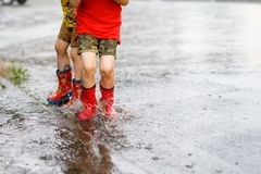 Two children wearing red rain boots jumping into a puddle. Close up. Kids having fun with splashing with water. Happy children during heavy summer shower rain Stock Photography