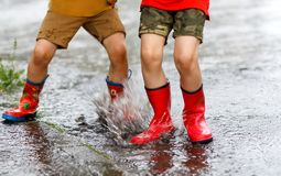 Two children wearing red rain boots jumping into a puddle. Close up. Kids having fun with splashing with water. Happy children during heavy summer shower rain Royalty Free Stock Photo