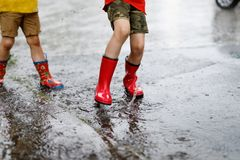 Two children wearing red rain boots jumping into a puddle. Close up. Kids having fun with splashing with water. Happy children during heavy summer shower rain Royalty Free Stock Images