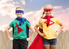 Two children wearing superhero costume standing with hands on hip. Against sky background Stock Image