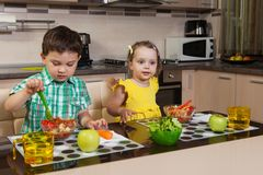 Two children who eat healthy food in the kitchen stock photos
