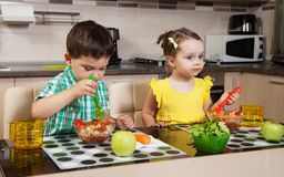 Two children who eat healthy food. In the kitchen stock photos