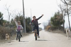 Two children who go with the bike to the camera stock image