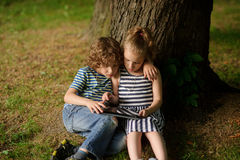 Two children of 7-8 years sit having inclined over the laptop screen. Stock Photos