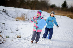 Two children of younger school age spend time in winter day with pleasure. Two children of younger school age, boy and girl, spend time in winter day with Royalty Free Stock Photos