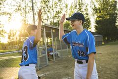 Two childrens baseball players standing together on the playground