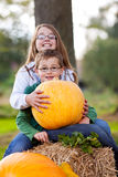 Two childrens happy with their pumpkin. Two children sitting on straw and holding a pumpkin Stock Photo