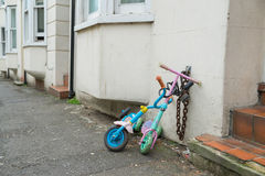 Two childrens scooters chained up in a street Stock Images