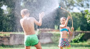 Two childs, brother and sister, have fun, when play with watering hose in summer garden royalty free stock photos