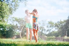 Two childs brother and sister play with watering hose in summer royalty free stock images