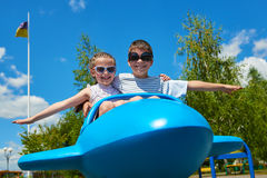 Two childs fly on blue airplane attraction in park, happy childhood, summer vacation concept Stock Images