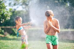 Two childs playing in garden, pours each other from the hose, makes a rain. Happy childhood concept image stock photography