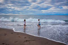 Two childs playing with waves royalty free stock photos