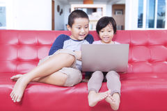 Two childs using laptop on couch at home. Portrait of attractive children sitting on sofa while using laptop computer to enjoy movie at home Stock Photo