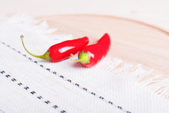 Two chili peppers on a cutting board with a napkin on a light wo Royalty Free Stock Photos