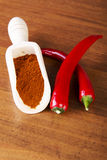 Two chili peppers with paprika spice. Stock Photos