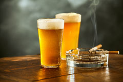 Two chilled beers with burning cigarettes Stock Photos