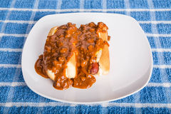 Two Chilli Dogs on White Plate and Blue Towel Stock Photo