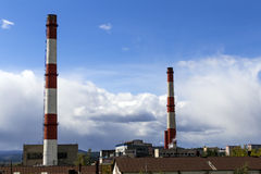 Two chimney-stalks. On a background cloudy sky Royalty Free Stock Images